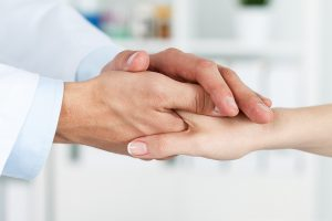 Male doctor's hands holding female patient's hand for encouragement and empathy.