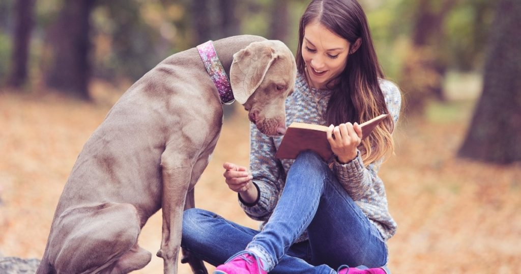 woman and dog reading book